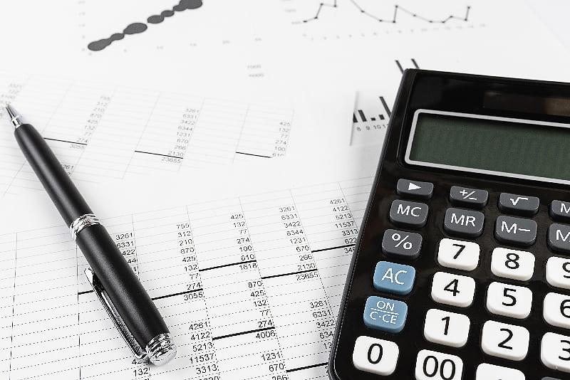 Kostenkontrolle mit Tabellen, Kugelschreiber und Taschenrechner