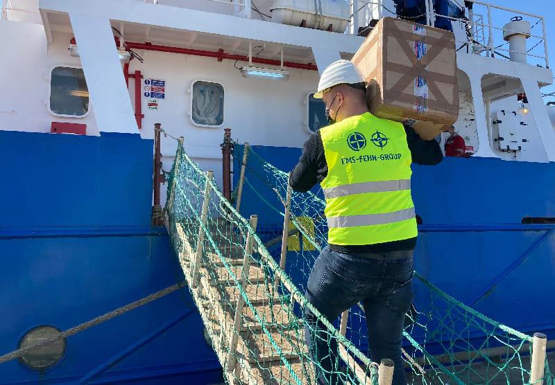 Mitarbeiter der Ems Fehn Group trägt einen Karton mit Proviant an Deck
