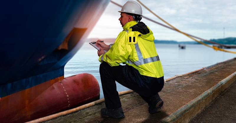 Ein Mitarbeiter von Fehnship in Sicherheitskleidung überprüft Schiffsteile auf Mängel